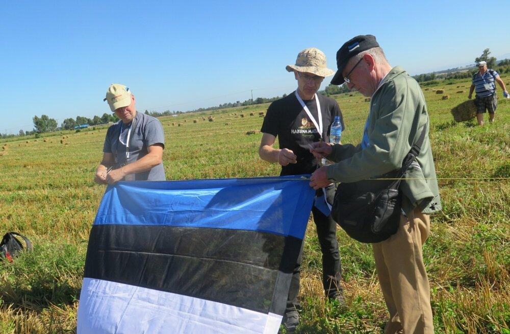 Fännid (vasakult) Jüri Kreintaal, Ain Kruusamägi ja Kalle Soover panid võistlusplatsi piirde külge Eesti lipu, mille varjus oli südapäeval hea end ekvaatoripäikese eest kaitsta.