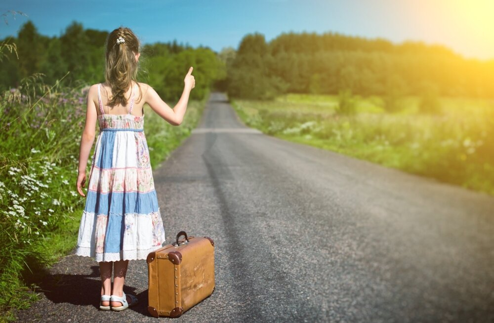 Little girl with vintage suitcase on rural road.