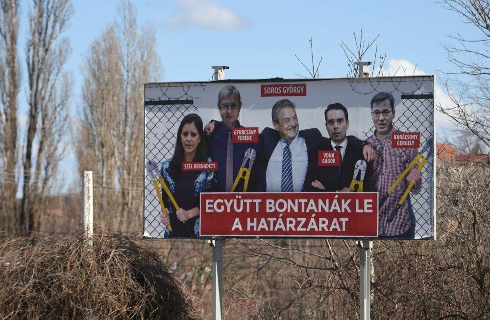 """Võimupartei Fidesz valimisplakat, mis kujutab miljardär George Sorost opositsiooniparteide esindajate keskel. Tekst ütleb: """"Nad võtaksid koos [piiri]tara maha."""""""