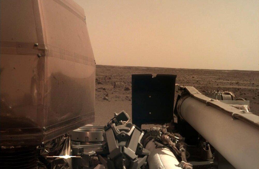 InSighti tehtud foto Marsilt, näha on maanduri instrumendid ning planeedi punane ja kivine pinnas