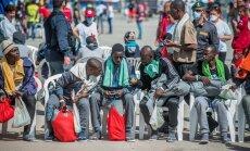 Sadamas antakse Aafrikast paljajalu saabunud põgenikele jalga plätud ning kätte kõrrejook, hall tekk ja punane kott asjade tarvis. Roheline rätik ja randmepael tähistavad haigeid.