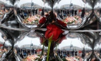 Jõuluootus ja lein. Breitscheidplatzi jõulukuulidelt peegelduvad Berliin, hukkunute mälestuseks toodud lilled ja vaikselt seisvad inimesed.