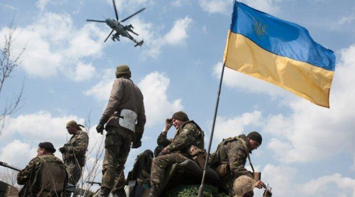 Десантники 25-й отдельной Днепропетровской аэромобильной бригады у Краматорска. В небе ударный вертолет Ми-24 с опознавательными знаками ВВС Украины.